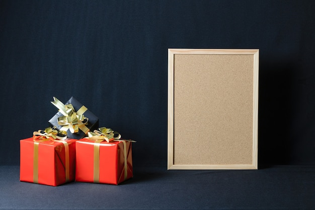 Corkboard and christmas gift boxes with copy space isolated on a dark background Free Photo