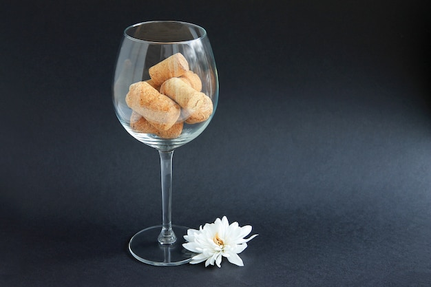 Corks from wine bottles are in the wine glass on a dark background Premium Photo