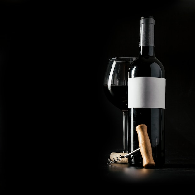 Corkscrew near bottle and glass of wine Free Photo
