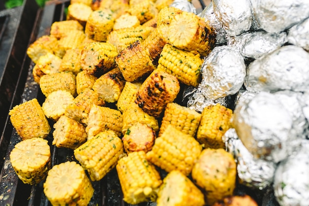 Corn cobs and potatoes wrapped in aluminum foil on a barbecue. Premium Photo