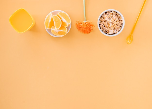 Corn flakes in bowl with orange and juice Free Photo