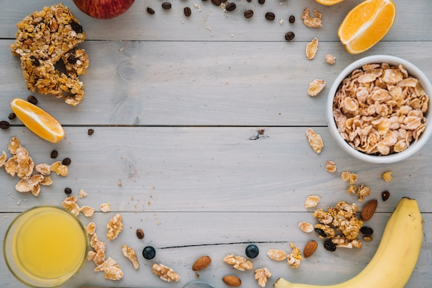 Кукурузные хлопья в миске с фруктами и соком на столе Premium Фотографии