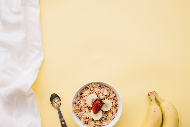 Corn flakes with with fruits in bowl on table Free Photo