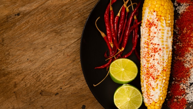 Corn on plate with limes and peppers Free Photo