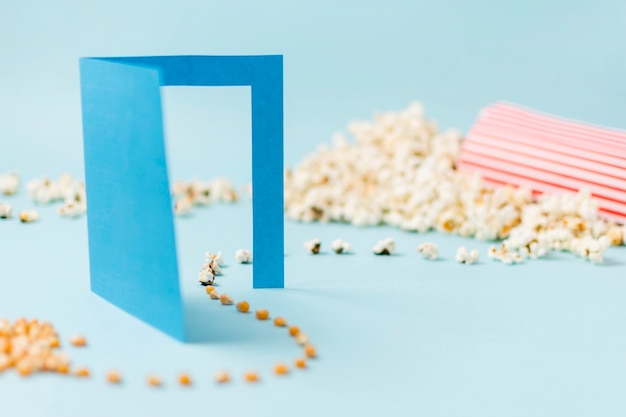 Corn seeds going through blue paper doorway turning into popcorn on blue backdrop Free Photo