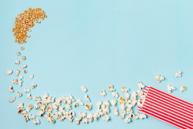 Corn seeds turns into popcorns enter in the popcorn box against blue backdrop Free Photo