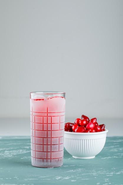Ягоды кизила в миске с видом сбоку напитка на гипсе и белом Бесплатные Фотографии