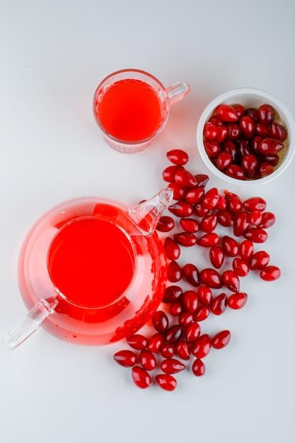 Ягоды кизила в миске с видом сверху напитка на белом Бесплатные Фотографии