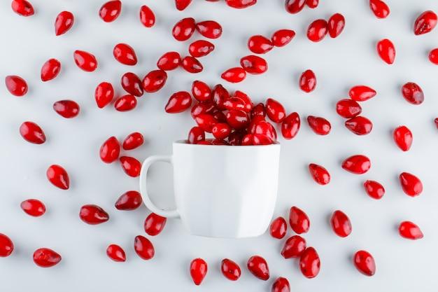 Ягоды кизила в чашке на белом Бесплатные Фотографии