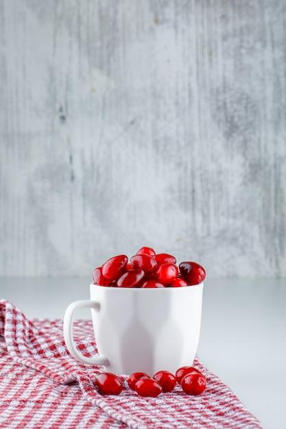 グレーと白のピクニック布の側面図とカップのコーネルベリー 無料写真