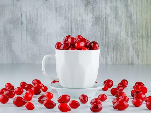 グレーと白の受け皿の側面図とカップのコーネルベリー 無料写真