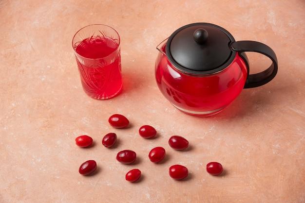 Ягоды кизила в чашке и сок в чайнике. Бесплатные Фотографии