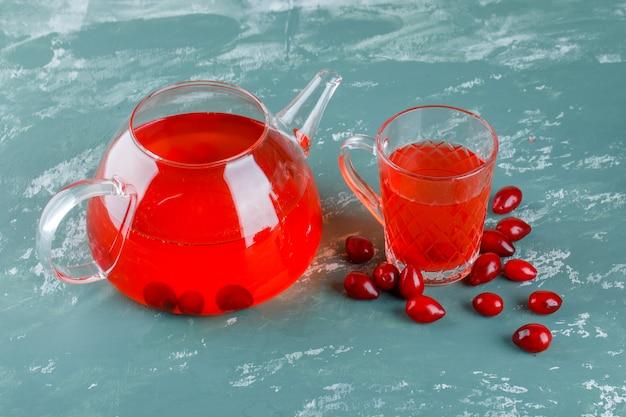 Ягоды кизила с напитком под высоким углом зрения на гипсе Бесплатные Фотографии