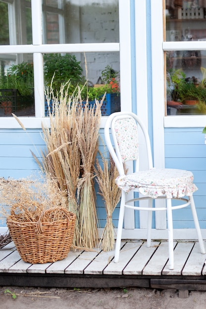 Corner of garden in fall. romantic porch, patio, chair and basket with spikelets near wooden blue house in countryside. terrace in rustic style. old coffee terrace, street cafe. modern interior design Premium Photo