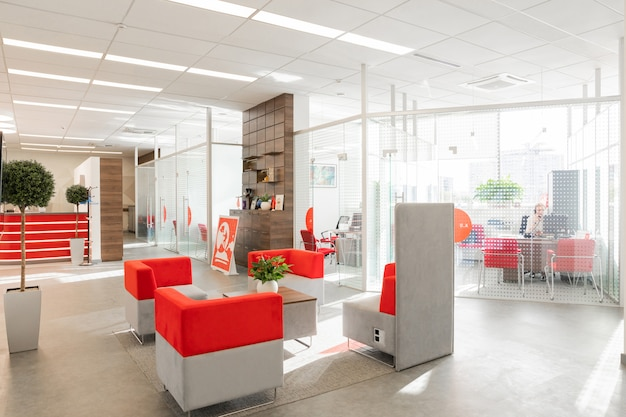 Corner of modern office with white walls, gray floor, open space area with red-white armchairs and rooms behind glass wall Premium Photo