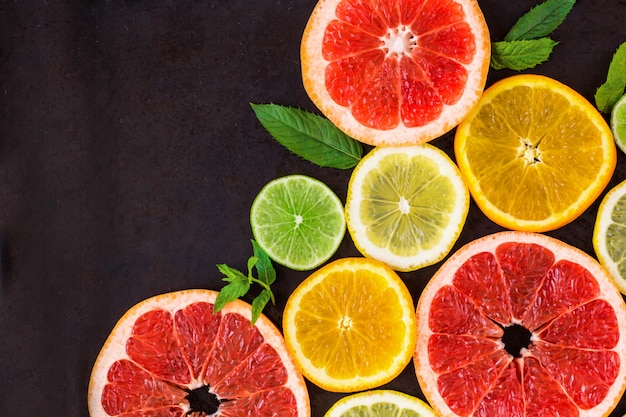 Corner with slice of oranges, lemons, limes, grapefruit and mint pattern on black. flat lay Premium Photo
