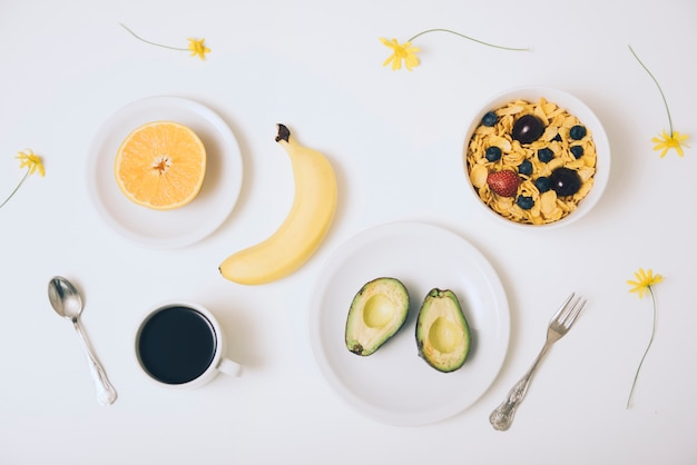 Cornflake cereals; avocado; banana; halved orange; coffee and flowers on white backdrop Free Photo