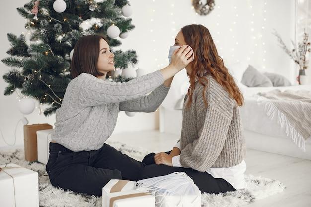 Коронавирус и рождественская концепция. женщина помогает подруге в маске. Бесплатные Фотографии