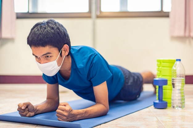 Coronavirus, asian man wear a mask and exercise alone in room at home to  preventing covid-19. workout from home, exercise from home. | Premium Photo