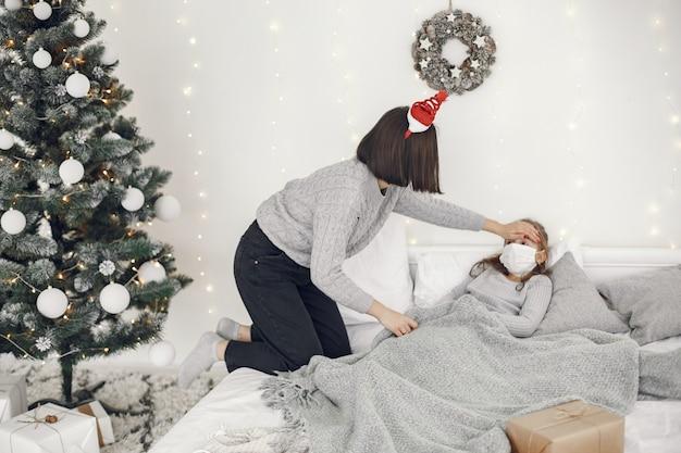 Coronavirus in un bambino. madre con figlia. bambino sdraiato in un letto. donna in una maschera medica. Foto Gratuite