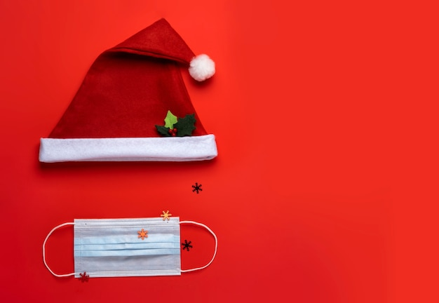 Coronavirus christmas background. santa claus hat and face mask on a red background. Premium Photo