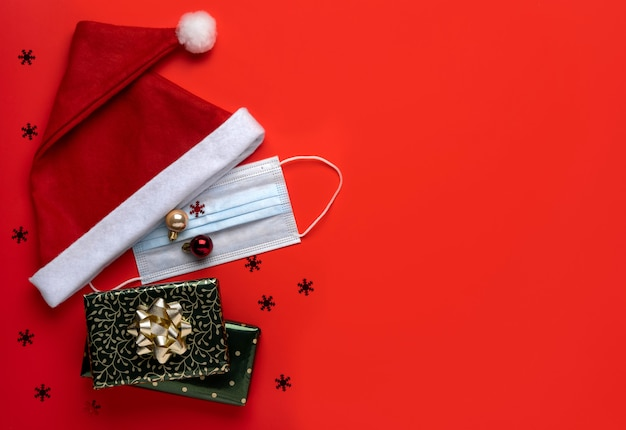 Coronavirus christmas background. santa claus hat and festive decorations with face mask on a red background. Premium Photo