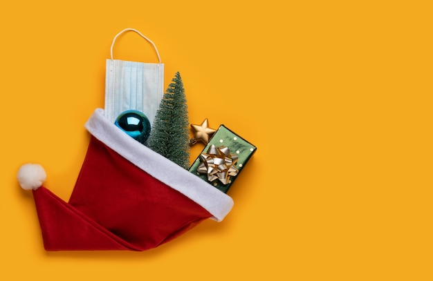 Coronavirus christmas background. santa claus hat and festive decorations with face mask on a yellow background. Premium Photo