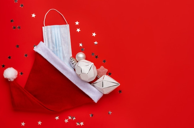 Coronavirus christmas background. santa claus hat with face mask on a red background. Premium Photo