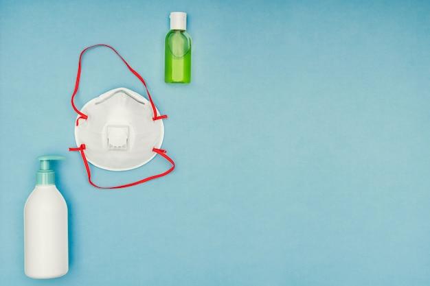 コロナウイルス、covid-19。防腐剤ジェル、液体私たち、青色の背景に保護マスク Premium写真