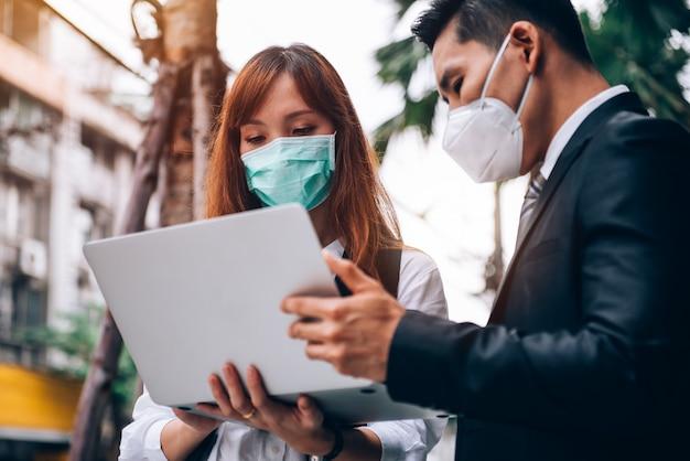 新しいビジネスのために屋外の場所で働いて調査しているアジアのビジネス人々、彼らはインフルエンザとcoronavirus covid-19を防ぐために保護マスクを着用しています Premium写真