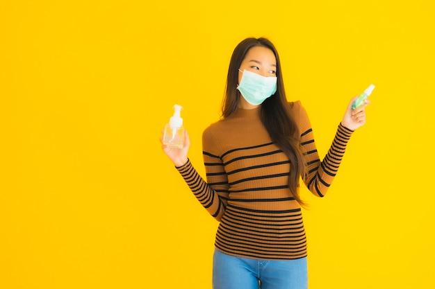 Женщина портрета красивая молодая азиатская с брызгом спирта маски и бутылкой геля в ее руке для защищает от coronavirus или covid19 Бесплатные Фотографии