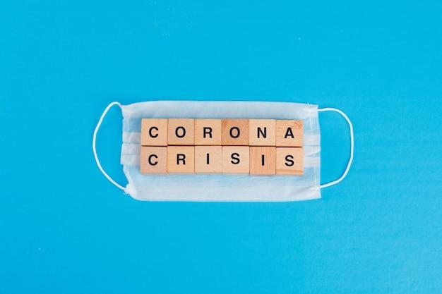 Concetto di crisi del coronavirus con la maschera medica, cubi di legno sulla disposizione blu del piano della tavola. Foto Gratuite