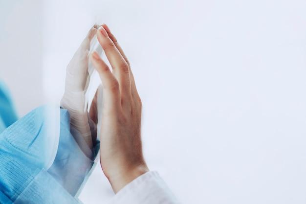 Medico del coronavirus che tocca la mano della famiglia attraverso una finestra di vetro Foto Gratuite