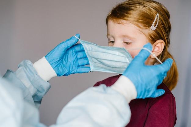 コロナウイルス。看護師、防護服の医者は、子供のために顔に医療マスクを置きます。 covid-19感染に対する予防策。インフルエンザ、コロナウイルスの流行に対する保護の概念。 Premium写真