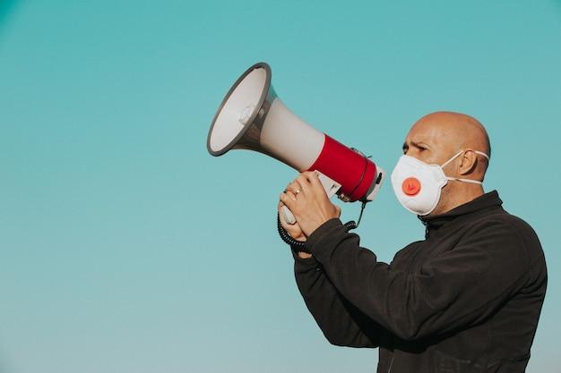 Coronavirus outbreak, angry man with medical face mask screaming into the megaphone, coronavirus, covid-2019 protest, economic crisis, worldwide pandemic Premium Photo