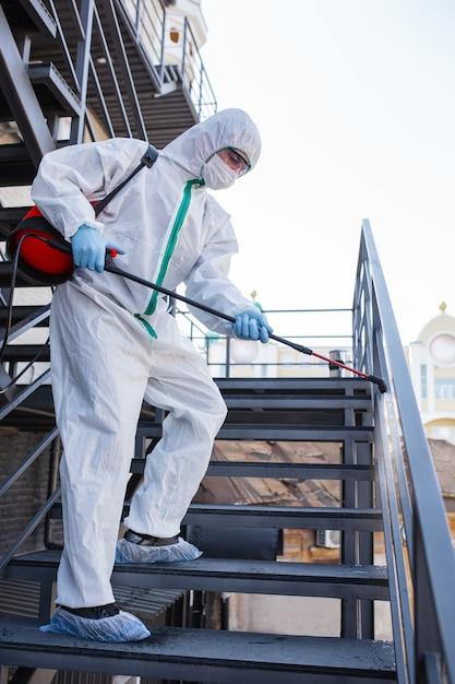 Pandemia di coronavirus. un disinfettante in tuta protettiva e maschera spruzza disinfettanti nella stanza. Foto Gratuite