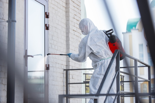 Coronavirus pandemic. a disinfectant in a protective suit and mask sprays disinfectants in the room. Free Photo