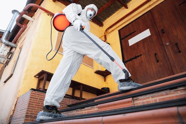 Коронавирус пандемия. дезинфектор в защитном костюме и спреи-маски дезинфицирующие средства в доме или офисе Бесплатные Фотографии