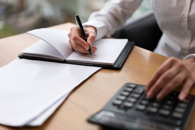 Corporate woman calculating and writing Free Photo