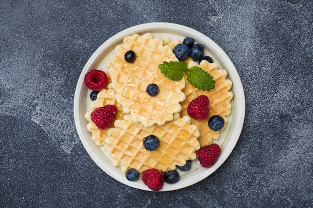 Corrugated waffle cookies with fresh raspberries and blueberries on a dark concrete surface Premium Photo