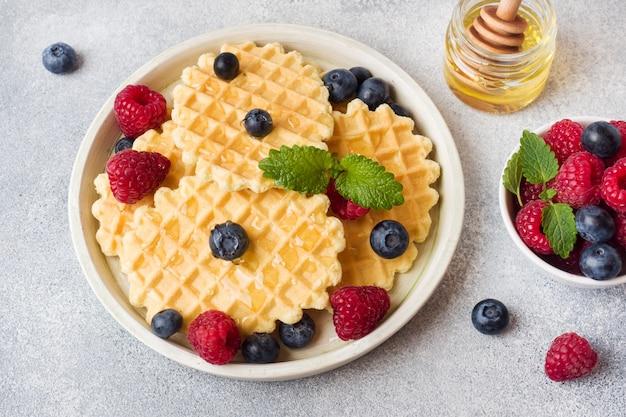 Corrugated waffle cookies with fresh raspberries and blueberries Premium Photo