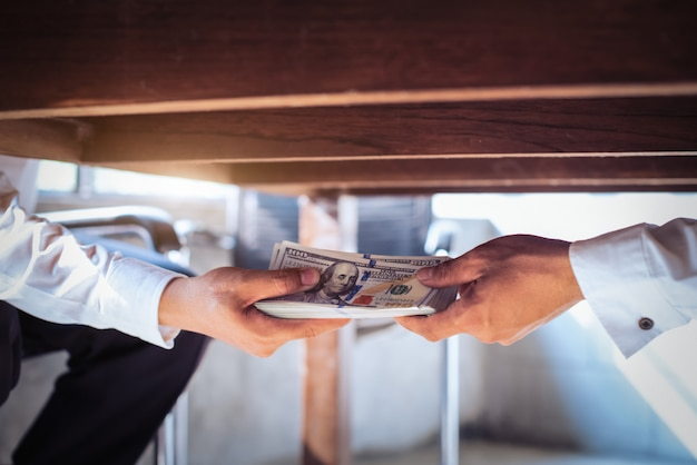 Corruption concept, businessman taking bribe from man under table Premium Photo