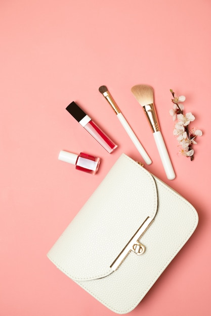 Cosmetic bag with beauty accessory and makeup product. flat lay Premium Photo
