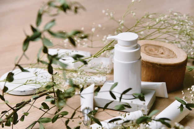 Cosmetic bottle containers packaging with green herbal leaves, blank label for organic branding , natural skincare beauty product concept. Premium Photo