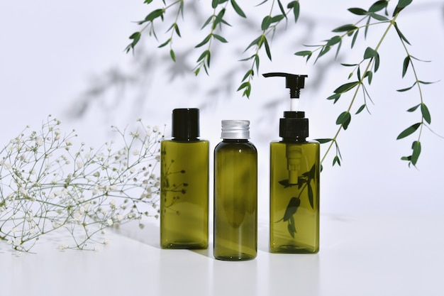 Cosmetic bottle containers packaging with green herbal leaves in shadow and light effect, blank label for organic branding , natural skincare beauty product concept. Premium Photo