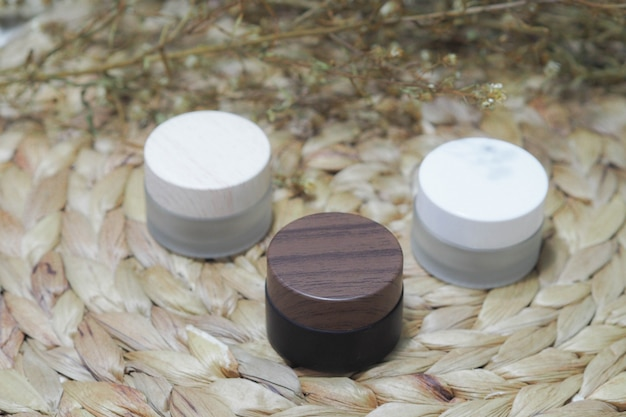 Cosmetic bottle containers white,brown,cream product with dry flower. Premium Photo