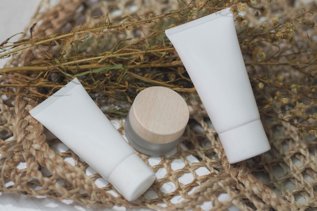 Cosmetic bottle containers white,cream product with dry flower and woven handbags. Premium Photo