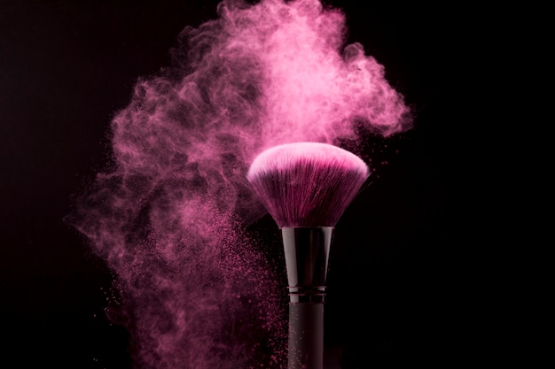 Cosmetic brush in cloud of pink powder on dark background Free Photo