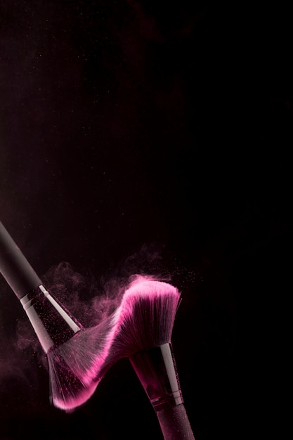 Cosmetic brushes in dust of powder on dark background Free Photo