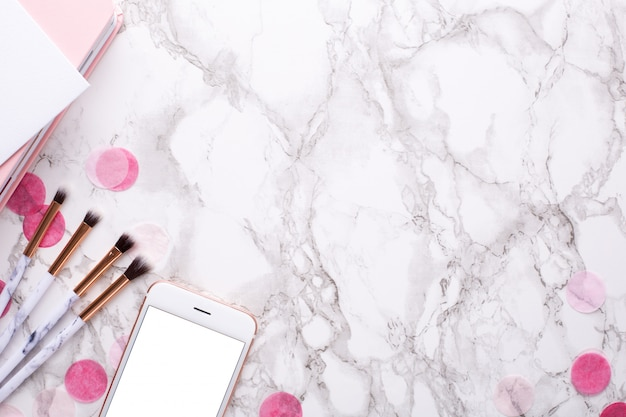 Cosmetic brushes and mobile phone on marble Premium Photo
